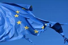 l-union-européenne-douze-tiennent-le-premier-r-le-le-drapeau-déchiré-et-avec-des-noeuds-dans-le-vent-sur-le-ciel-bleu-75163975.jpg