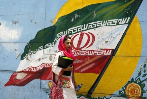 iranienne-marche-devant-le-drapeau-national-peint-sur-un-mur-de-teheran-le.jpg