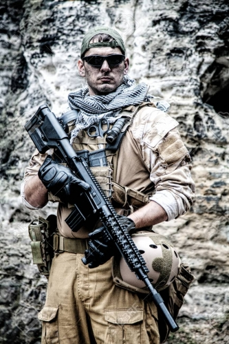 96004499-private-military-contractor-pmc-in-baseball-cap-with-assault-rifle-in-the-rocks.jpg