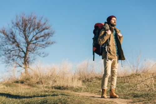 hipster-man-traveling-with-backpack-autumn-forest-wearing-warm-jacket-hat-active-tourist-exploring-nature-cold-season_285396-1574.jpg
